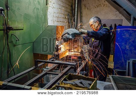 Voronezh, Russia Circa 2017: Metal worker cutting metal parts using electric circular grinder in metalwork factory. Sparks while grinding.