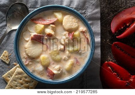 A bowl of delicious homemade seafood chowder with lobster scallops haddock clams and potato.
