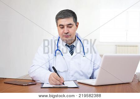 A doctor works in the office at a computer and writes in a workbook