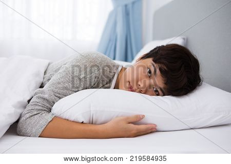 Tired Asian woman preparing to sleep in bed and looking at camera. Unsmiling young woman embracing pillow while lying in bed. Bedding concept
