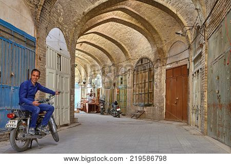 Yazd Iran - April 22 2017: One middle-aged smiling man an Iranian ethnos sideways sat in the saddle of motobike in the vaulted corridor of the eastern bazaar.