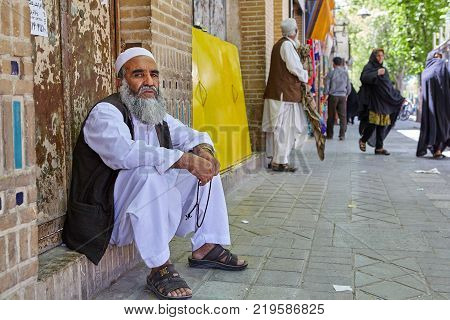 Yazd Iran - April 22 2017: An elderly bearded man in white Muslim clothes fingering rosary sitting on the threshold of a brick house on a busy street.