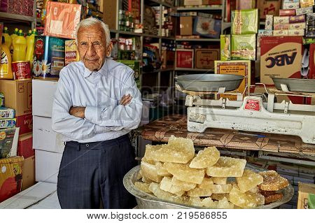 Yazd Iran - April 22 2017: One unknown elderly grocer stands with his arms crossed near the pelvis with yellow rocky sugar.