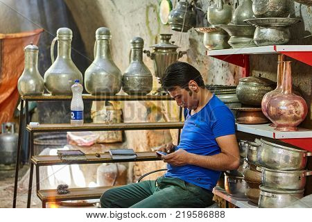 Yazd Iran - April 22 2017: A young man uses a smartphone while sitting on a chair in a tin shop.