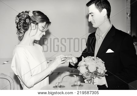 Wedding ceremony in black and white - exchange of engagement rings at the solemn marriage registration of newlyweds. Selective focus.