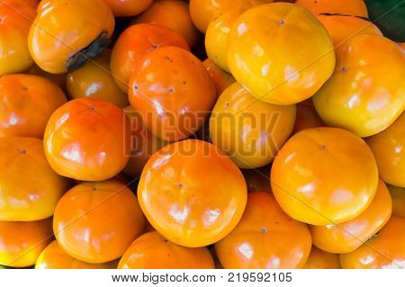 Orange persimmon on the floor.Persimmon background. Orange ripe persimmons tiled on a market stall. Organic persimmon fruits in pile at local farmers market. Persimmons fruit at the farmers market,Persimmon, The stage of fresh Persimmon in the fruit marke