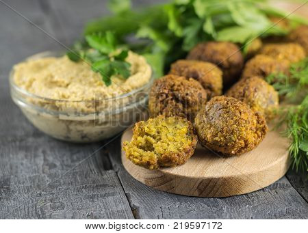 Freshly cooked falafel on lettuce leaves on a dark wooden table with tahini sauce. Eastern vegetarian meal of chickpea.