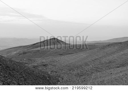 White and black sunrise in negev desert in Israel. Morning landscape of natural nature, sand and stones. Scenic land mountains and rocks in middle east. Nobody on photo