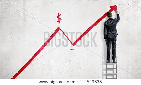 A businessman stands on a step ladder and draws a red statistic arrow moving up with a dollar sign. Business growth. Planning and strategy. Earnings and benefits.