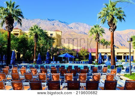 December 19, 2017 in Palm Springs, CA:  Lawn chairs beside a pool surrounded by palm trees at the Renaissance Hotel in Palm Springs, CA where people can sunbathe poolside while enjoying the surrounding gardens and the beautiful desert mountains beyond