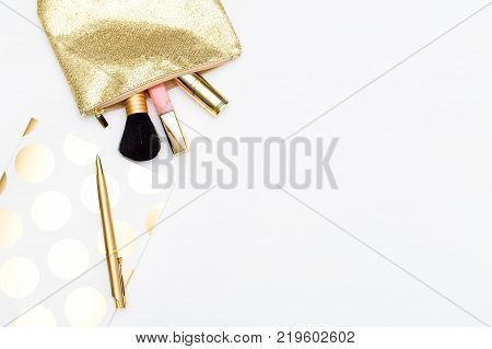 Cosmetics for make-up and notebook with pen in gold color on a white background. Copy space