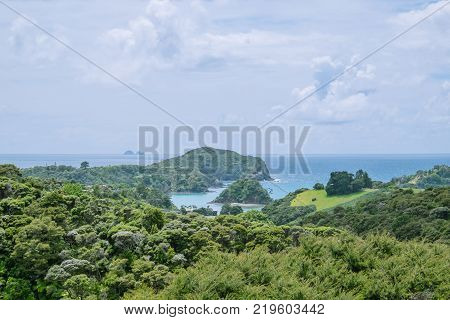 View over green bush landscape to Tutukaka Harbour and The Poor Knights Islands Northland New Zealand NZ
