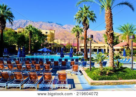 December 18, 2017 in Palm Springs, CA:  Lounge chairs and palm trees surrounding a pool taken at the Renaissance Hotel in Palm Springs, CA where guests can swim and sunbathe poolside while surrounded by beautiful desert gardens and mountains beyond