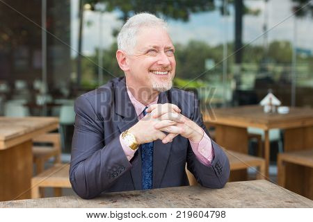 Closeup portrait of happy senior handsome man looking away with his hands clasped and sitting at table in outdoor cafe