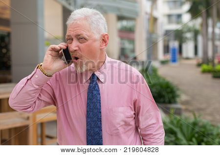 Closeup portrait of indignant senior handsome man talking on smartphone and standing on street in summer
