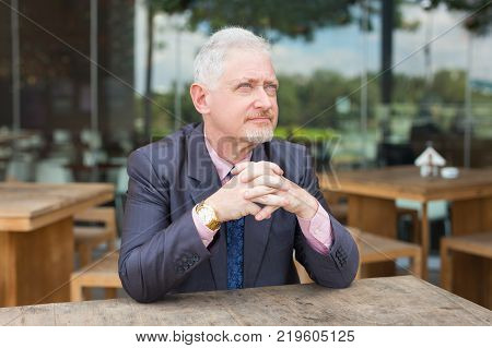 Closeup portrait of pensive senior handsome man looking away with his hands clasped and sitting at table in outdoor cafe