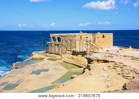 Salt pans along the waterfront with the Il-Qolla I-Badja battery to the rear Redoubt Marsalforn Gozo Malta Europe.