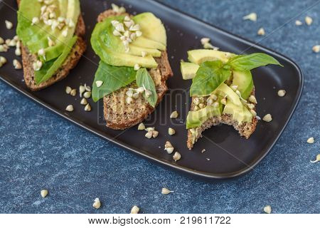 Avocado sandwich with basil and sprouts of green buckwheat on a black straight-headed plate bitten off piece dark blue background. Healthy vegan food concept.