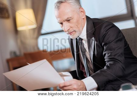 Contact review. Earnest  senior handsome man  regarding documents while sitting and looking down