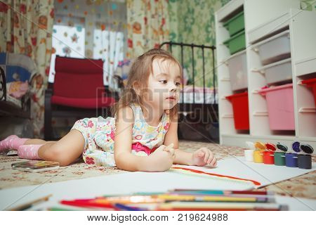 Little creative girl lies on kids bedroom floor surrounded with colorful pencils and bottles of bright gouache and aquarelle, and paints picture with brush in album.
