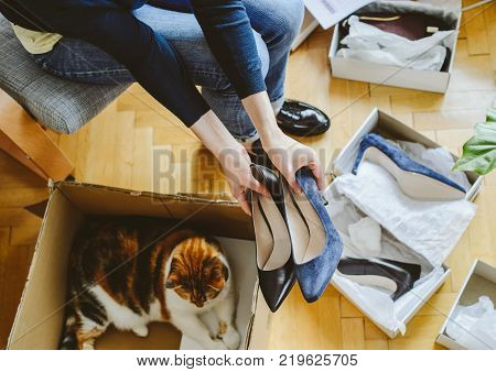 View from above of woman hand unboxing unpacking several pairs of new shoes bought via online store and curious cat pet inside the box cardboard