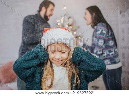 Sad, desperate little girl during parents quarrel. Clog the ears.. Family quarrel on the eve of Christmas