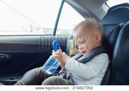 Cute little Asian 18 months / 1 year old toddler baby boy child sitting in car seat holding and drinking water from cup Happy traveling with child concept Little Traveler safety road trip concept