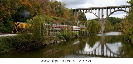 brightly colored train going under a bridge.  the bridge is reflected in the water. poster