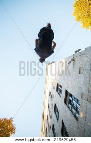 Young man doing a side flip or somersault while practicing parkour on the street.