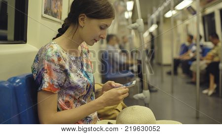 Young woman tourist travelling in subway and looking in map at smartphone in Bangkok subway