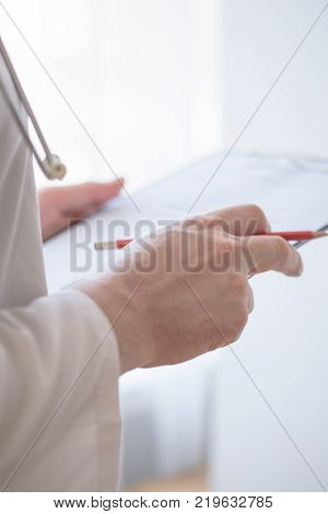 Close-up Of Male Doctor Filling The Medical Form. Doctor writting. Uniform doctor. Doctor man. Doctor woman. Doctor paperwork. Pen in hand doctor.
