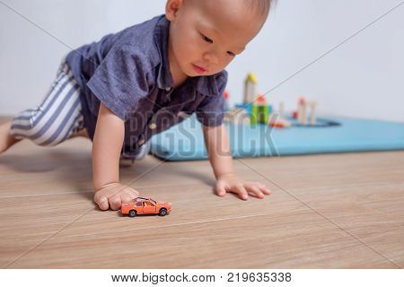 Cute little Asian 20 months / 1 year old toddler baby boy child playing with toy car in living room at home selective focus at orange small toy car Kid under 3 years old play with small parts toy