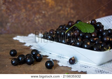 Fresh Berries Of Black Currant In Ceramic  Bowl On Metal Background. Ribes Aureum Known By The Commo