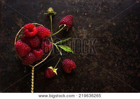 Raspberries With Spoon. A Fresh Raspberry On A Wooden Spoon. Ripe Fresh Raspberries With Leaves On R