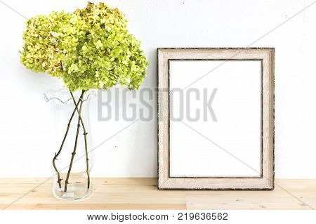 Wooden frame mockup with green flowers. Poster product design styled mock-up.