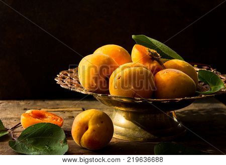 Apricots And Its Cross-section On The Old Wooden Table. Darck Moody. Apricots And Its Cross-section