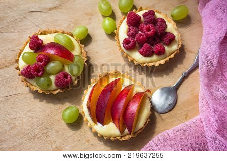 Raspberry tart dessert on dark background. Traditional french sweet pastry. Delicious appetizing homemade cake with custard fresh berries and fruits. Copy space closeup.