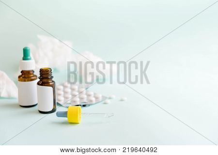 Spray for the nose or a pill to treat colds and gripes. Glass Bottle with medicines and paper handkerchiefs on a green background. Copy space for text
