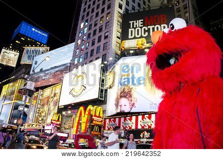 Times Square, New York City, New York, United States - circa 2015 - sesame street elmo character in costume times square night new york city with bright advertising signs