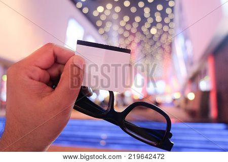 3d glasses with tickets in young hand man with cinema background