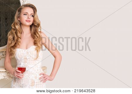 Elegant blonde lady with glass of wine. Beautiful sexy young woman with long hair perfect body and pretty face make-up in evening dress drinking alcohol in light luxury interior. Copyspace for text