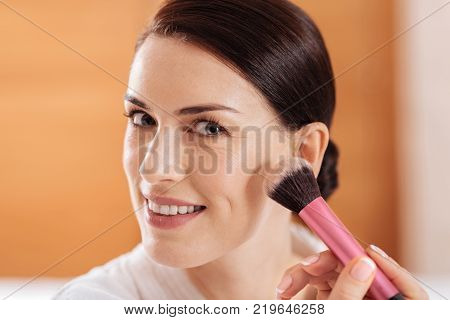 Daily makeup.  Close up of irresistible wonderful gay woman holding tassel while looking at the camera and smiling