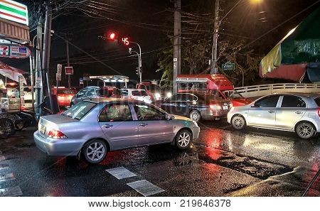 BANGKOK THAILAND - DECEMBER 26: Rush hour communiters commits moving traffic violation by running a red light and completely blocking off an intersection in a traffic jam in Bangkok on December 26 2017.