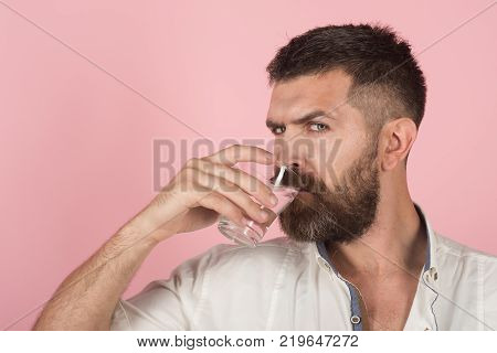 man with beard on face drink water from glass on pink background healthcare and life source hangover and thirst refreshing copy space poster