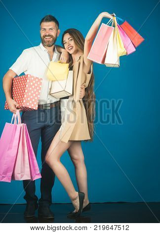 Black Friday happy holiday relations. Shopping and sale. Couple in love hold shopping bag near blue wall. Fashion shopaholic couple. Girl and bearded man hold present pack cyber Monday copy space