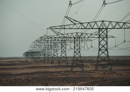 Electric energy transmission. Electricity distribution stations. Global warming climate change. Ecology eco power technology concept. Power line towers in desert on blue sky background.