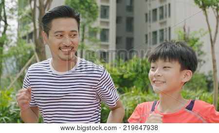 portrait of Chinese man & his son smiling & jogging in garden in the morning