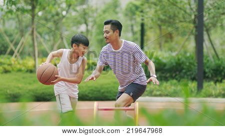 Chinese father & son playing basketball in garden in morning