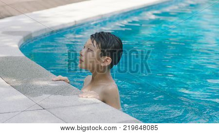 portrait of Asian teenage boy swimming outdoors in blue pool in summer