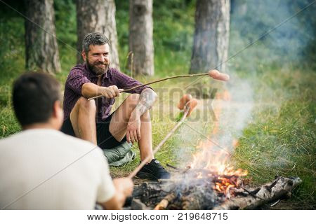 Friends men roast sausages on sticks on campfire in forest. Summer camping hiking vacation. Picnic barbecue cooking food concept.